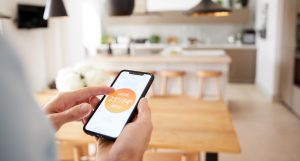 Close Up Of Man Using App On Smart Phone To Control Central Heating Temperature In House